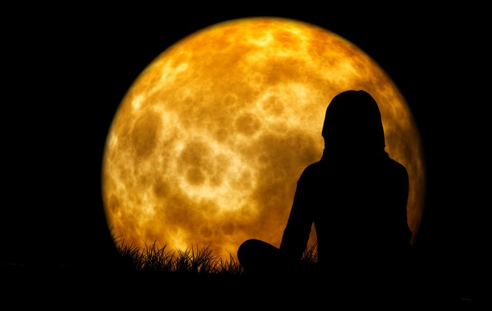 woman contemplating full moon