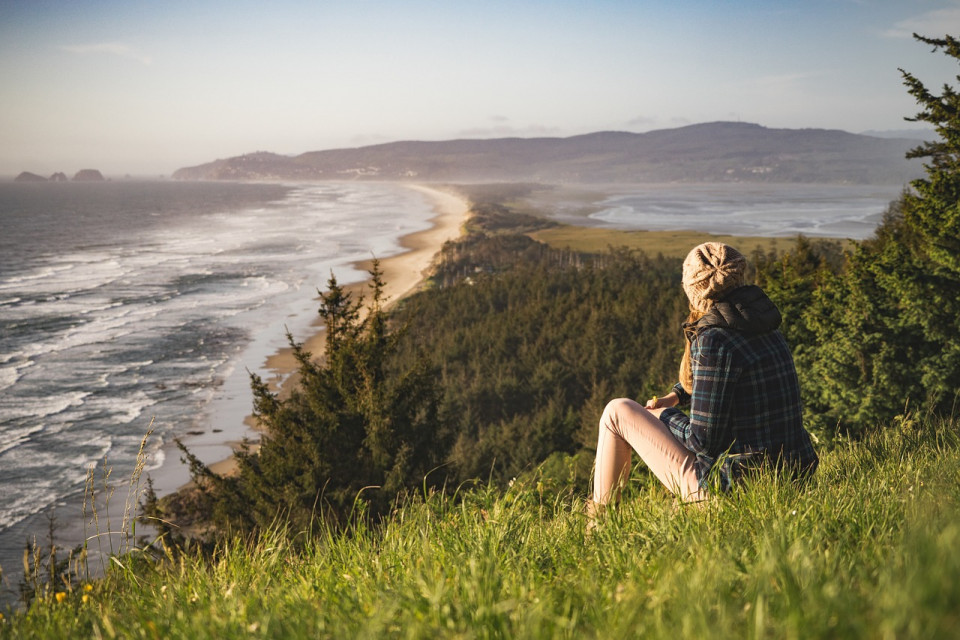 woman on a hill looking down at a mountain beach