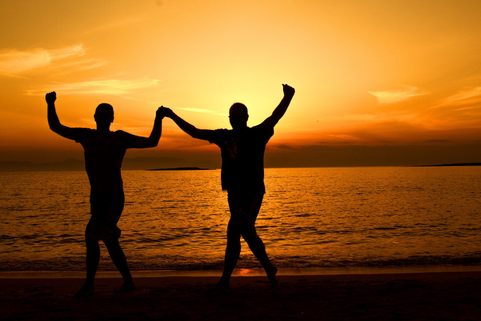 men dancing beach sunset