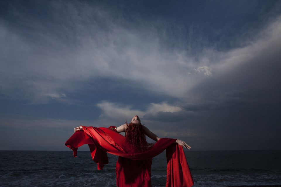 woman with red fabric and sky