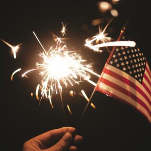 sparkler and US flag in night sky
