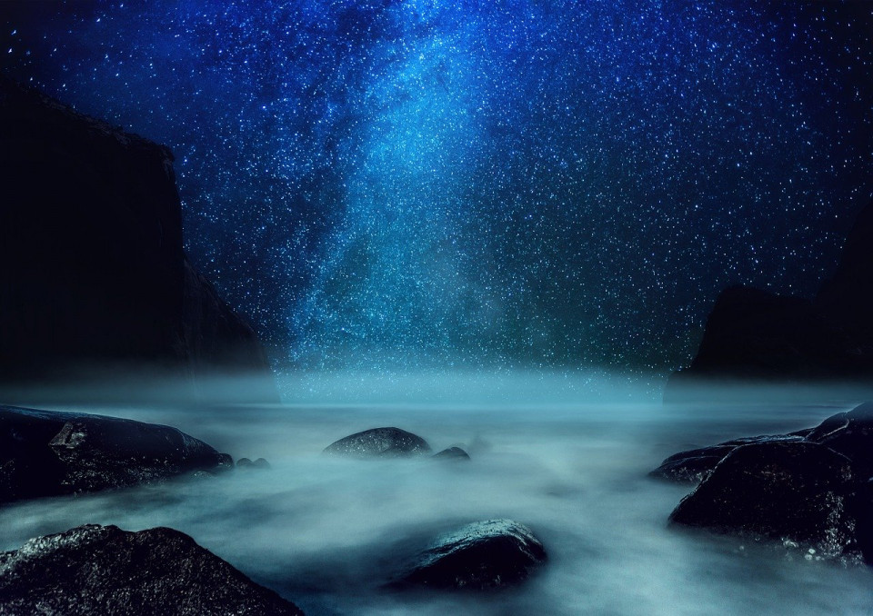 photo of light beaming from night sky into water
