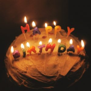 photo of a cake with lit candles spelling happy birthday