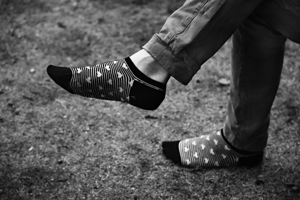 b&w photo of a man's legs and feet wearing socks with hearts Image by Mabel Amber from Pixabay