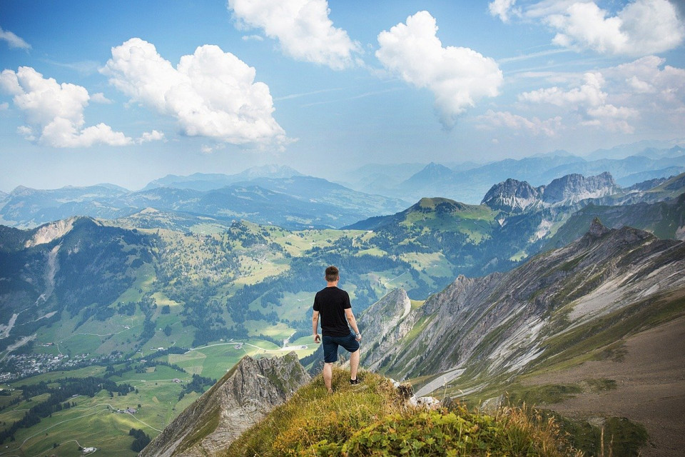 photo of a man on a mountain looking into a mountain panorama Image by Free-Photos from Pixabay