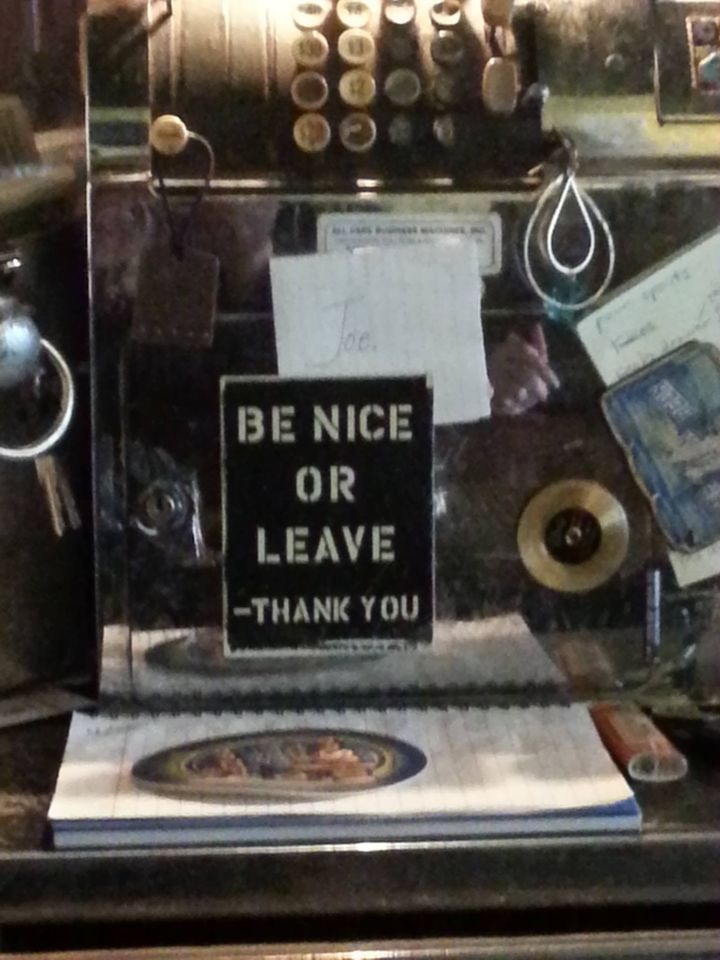 photo of a sign in a Soho bar that says Be Nice of Leave