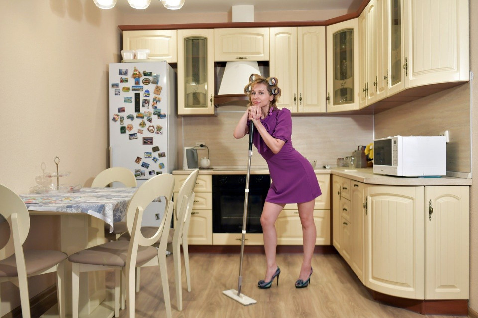 photo od woman leaning on a mop in a small kitchen
