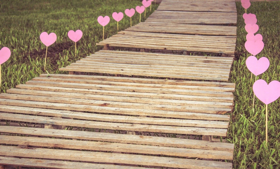photo of wooden walkway across grass with little hearts posted alongside Image by Mariangela Castro (Mary) from Pixabay