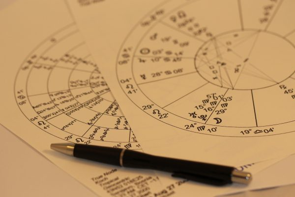 photo of astrology charts with a pen