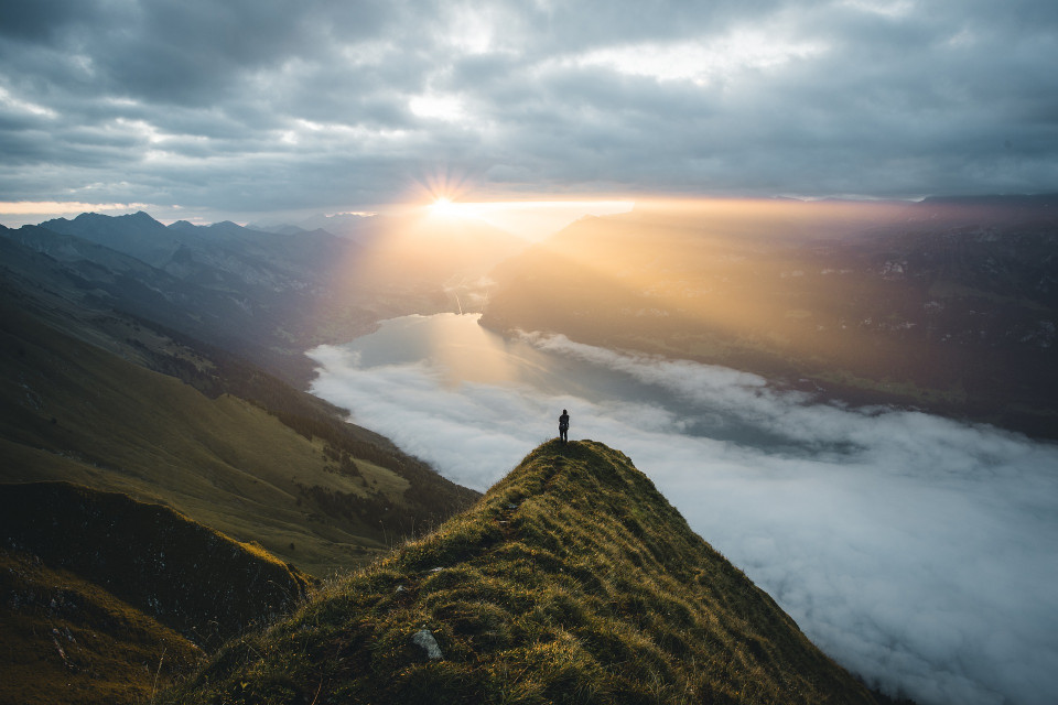 photo of a mountain river valley with a person far off and sun coming through clouds Image by Mrexentric from Pixabay