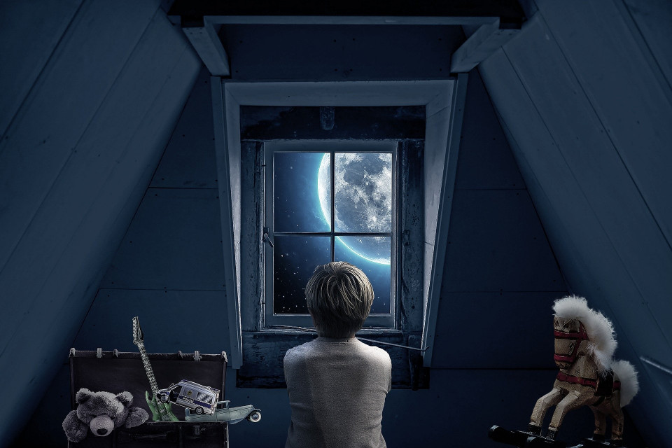 image of a boy in an attic with toys in a box and looking out the window at the moon at night Image by Myriams-Fotos from Pixabay