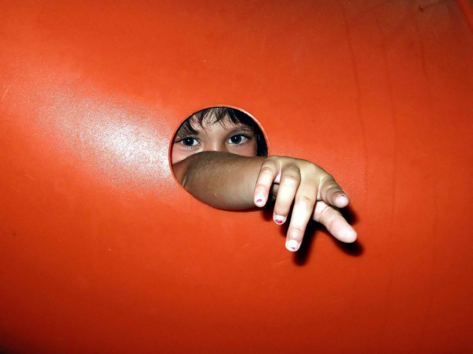 photo of orange barrier with child reaching through a round hole