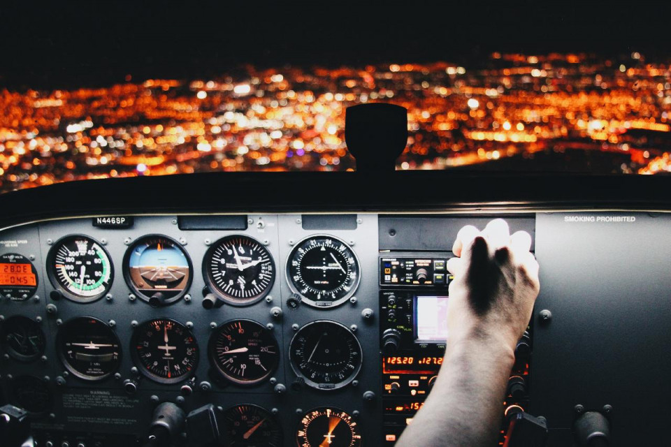 photo of an airplane cockpit with hand on control flying about lights on the ground at night