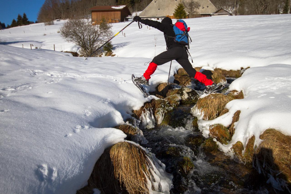 photo of hiker in snow jumping over a rocky creek