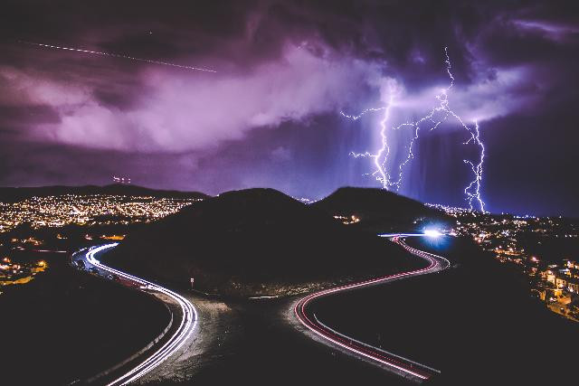 photo of landscape with two roads and lightning hitting ground in the distance