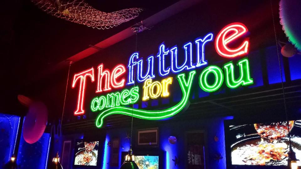 neon lights spelling The future comes for you over a store