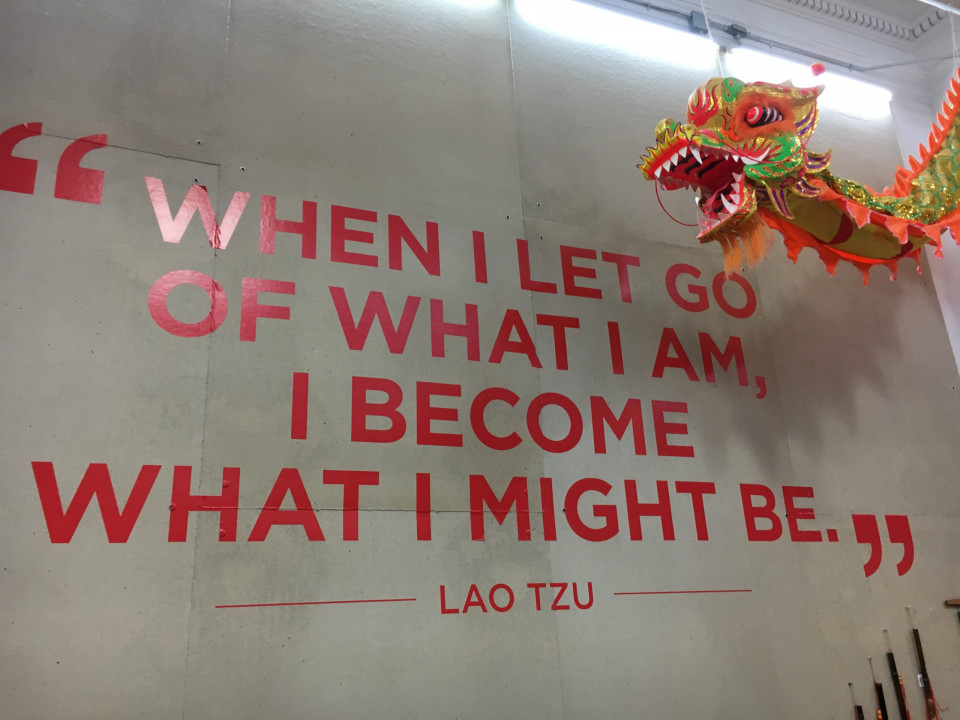 photo of a marble wall with red capital letters WHEN I LET GO OF WHAT I AM, I BECOME WHAT I MIGHT BE -- Lao Tzu with a red dragon head hanging in upper right