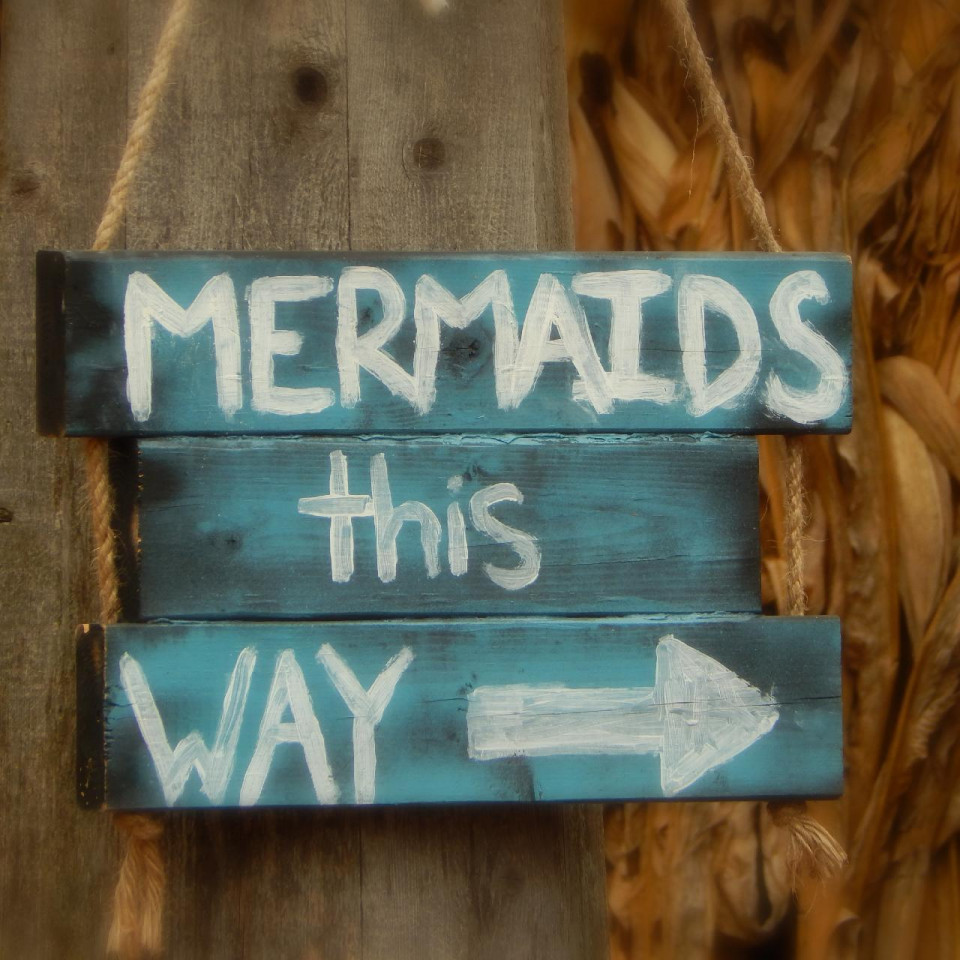 photo of three boards painted blue with white stacked words MERMAIDS this WAY and white arrow pointing right