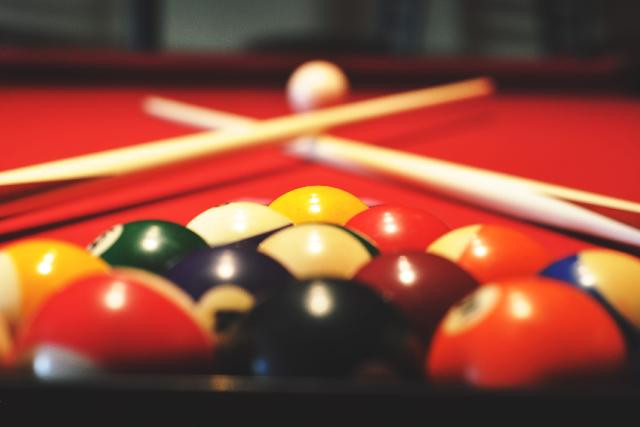 photo of pool cue balls with crossed cue sticks