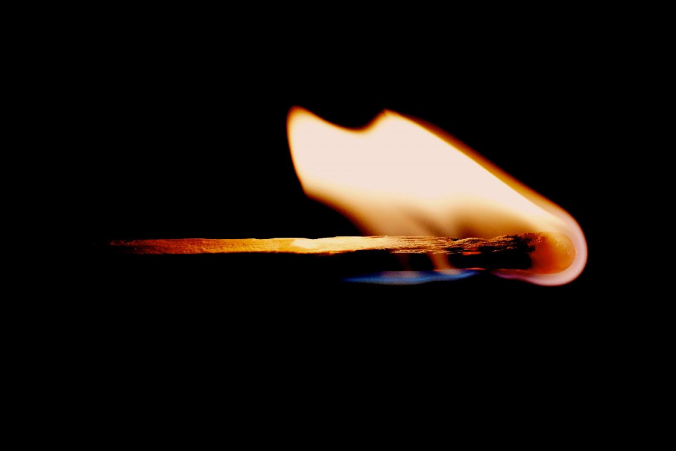 photo of a burning match against a dark brown background