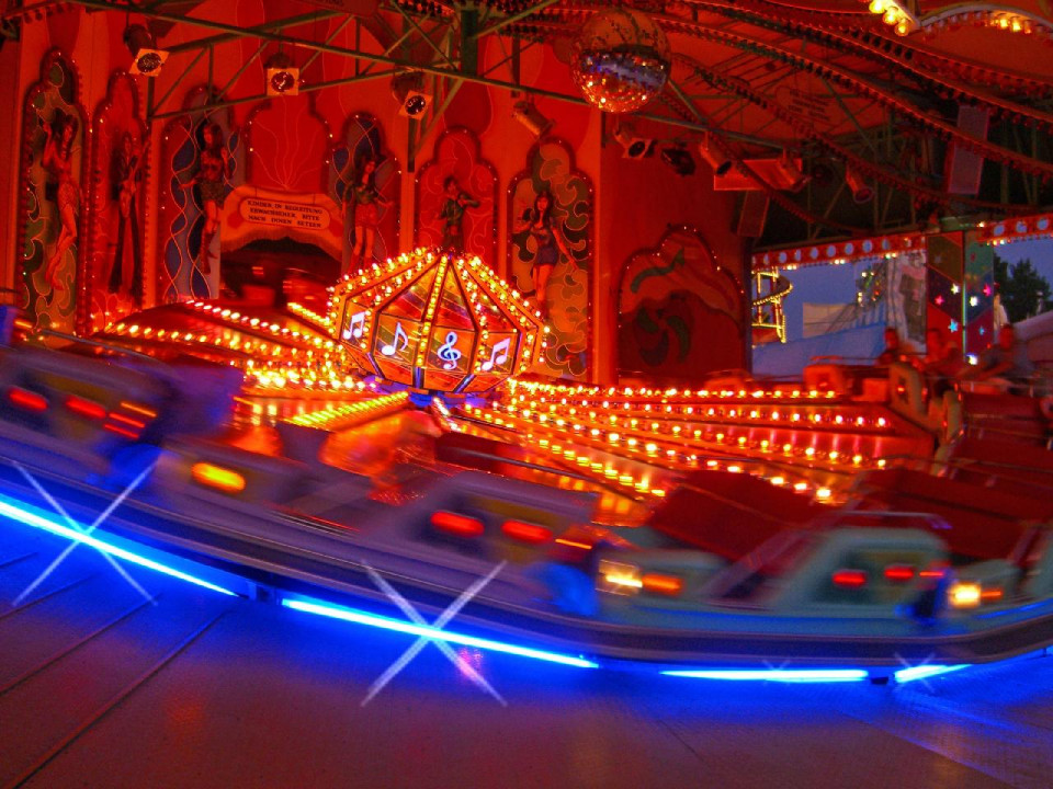 blurred time lapse photo of an amusement park ride with red neon spokes coming out from a neon globe at the center on a round titled track and blue neon lining the bottom, with red neon shapes barely discernible in the background