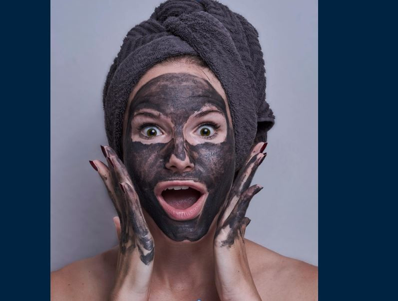 photo of a woman wearing a brown towel turban and with a brown mud mask on her face and hands (alongside her face) with mouth and eyes wide open looking surprised