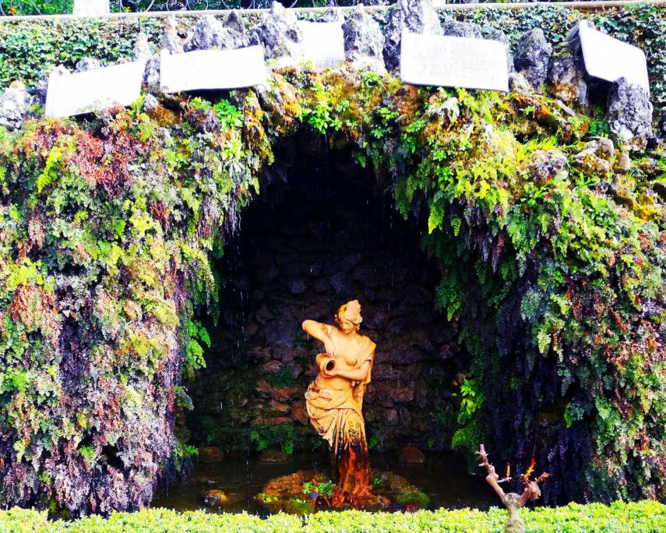 photo of a cave opening, with green goilage growing on the outside and white prayer flags posted over the opening, showing a dark cavern and a white statue of a woman pouring an urn