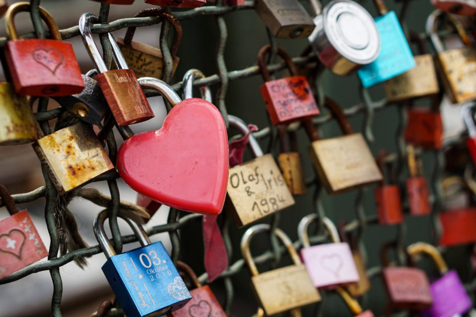 close up photo of locks on a chain link fence, One large red heart lock in center left; the rest are rechangular locks in red or gold or blue