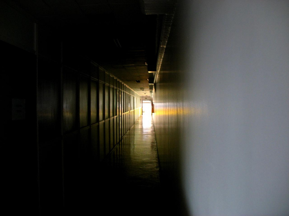 photo of narrow corridor, white and blurred on right and dar brown with paneled wall on left and ceiling, leading to a rectangle of light through an open retange at the center background and light reflecting on the ceiling, left wall, floor and right wall