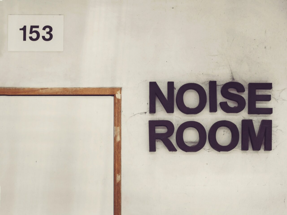 photo of a dirty white wall, with a whiter rectangle and the numbers 153 in black above a partial view of a wooden door frame, with the top extending horizontally 1/3 down into the middle and then going down, and large capital letters to the right spelling NOISE and below that ROOM