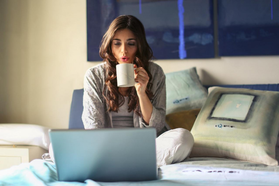 photo of a Caucasian woman in white colored pajamas with long brown hair holding a white mug to her mouth and sitting cross-legged on a crfeam colored bed with a grey pillow behind her and a grey open laptop in front of her