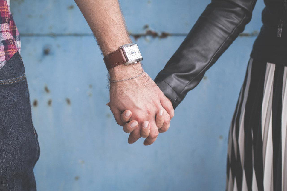 photo of a bare male arm from mid down and wearing a rectangular watch with a wide brown band holding hands with a female arm wearing a long-sleeved charcoal colored top against a steel gray wall