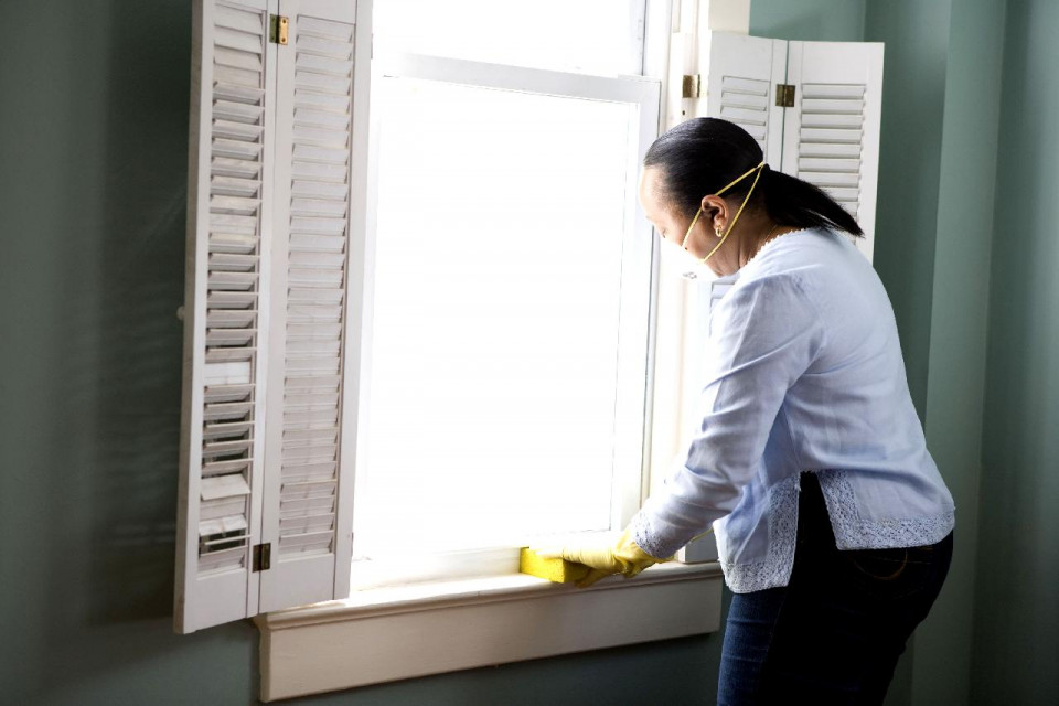 photo of a woman shown three-quarters view from the left side with dark brown hair pulled back and wearing a white face mask, long-sleeved light blue shift, dark flue jeans and yellow gloves, holding a rectangular yellow sponge against the wooden sill of a window with bright white light coming through the glass and white shutters on either side, in a room with sage green walls