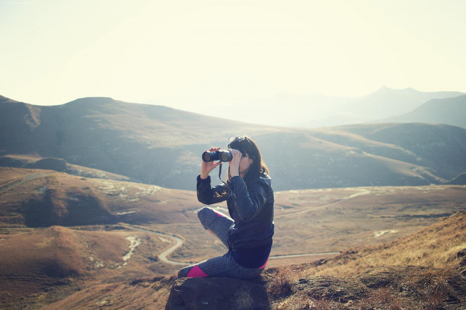 photo of a woman kneeling on rocky ground, shown from the side, wearing black, holding binoculars and looking to the left, in front of a rolling hill with a larger rolling hill in the background and the top third of the image white sky