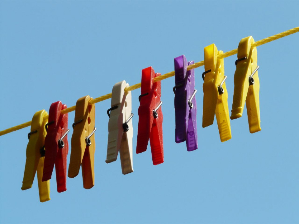 photo with blue black and eight clothes pins (yellow, red, light brown, white, red, purple, yellow and yellow)on a yellow rope