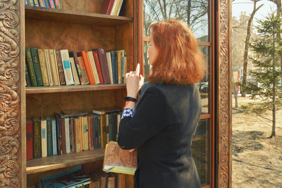 photo of woman with shoulder length red hair in tailored dark green jacket, viewed three quarters left profile from behind, with left arm bent and index finger raised, looking at a bookshelf with four shelves filled with hardcover books within an ornately carved snad colored archway and outdoors visible to her right with close cut green grass and a fir tree at the far right