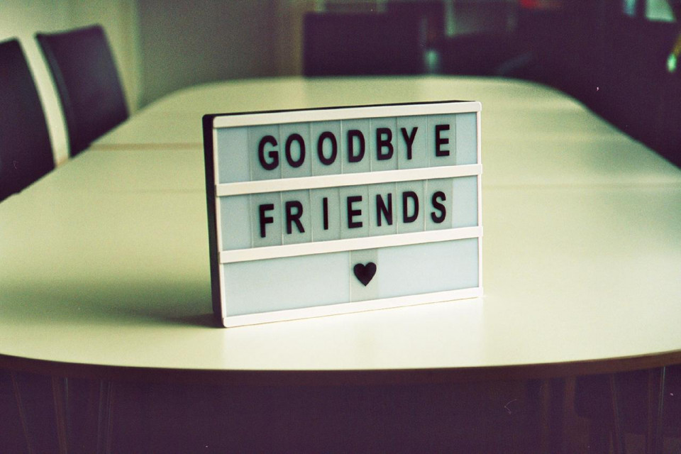 blurry slightly green tinted photo of a long white rectangular table with rounded edges, three tall brown backed chairs visible and a rectangle white sign with capital letters spelling GOODBYE FRIENDS with a black solid heart under the E in FRIENDS
