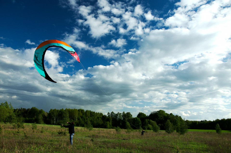 color photo with top 2/3 showing a blue sky with thick low white clouds, a green oen field with tall green trees in the background and a figure wearing a black jacket and blue jeans and above it a kite in a rounded arch with a dark blue bottom edge, aqua colored middle and a red accet on the top and right tip