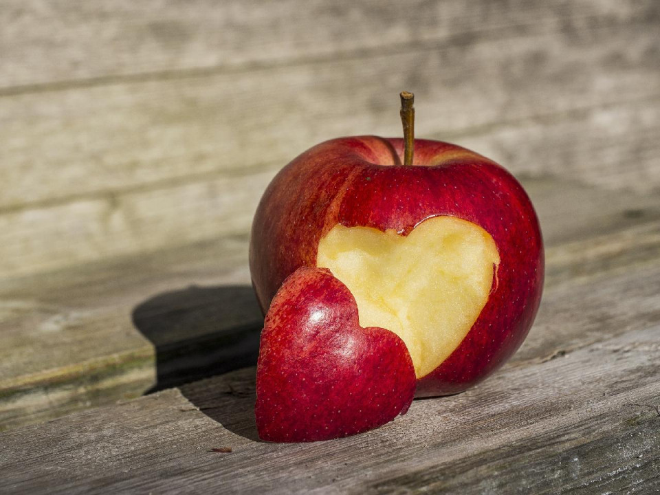 photo of a red delicious apple with brown stem and a heart shaped section cut from the front, with the heart next to the opening with the rounded parts tilting up and to the right, on two three weather worn brown wooden slats with three slats visible in the background