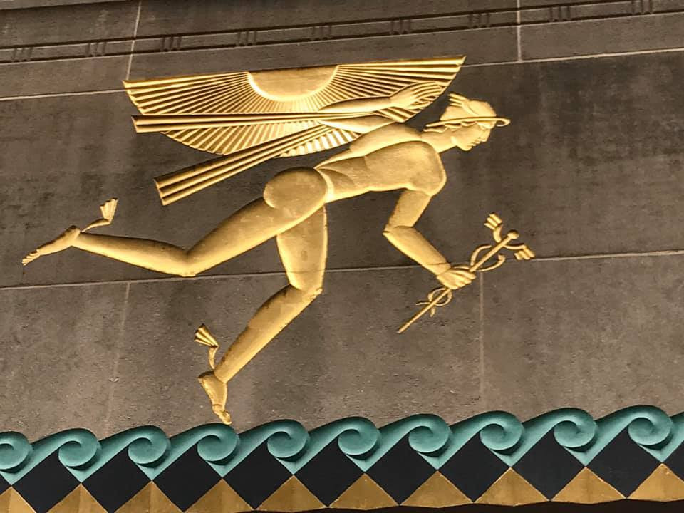 photo of messenger god Mercury in gold relief with winged cap and sandals and holding a cadeceus in his right hand and bending forward, on the wall at Rockefeller Center, with blue curling save and dark brown diamonds beheath his left foot