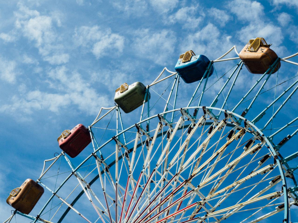 photo of blue sky with wispy clouds and the upper half of a ferris wheel showing four cars (orange, red, green, ble and gold) at the top