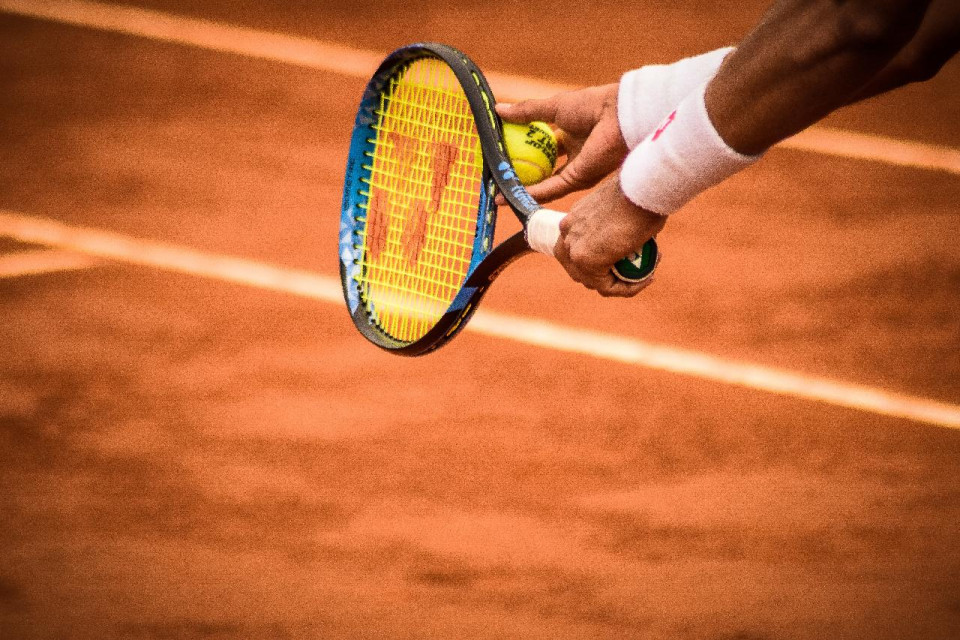 color photo of a man's forearms with white sweatbands , a tennis racket in the left hand and a yellow tennis ball in ther ight, with a clay court with two diagonal white lines